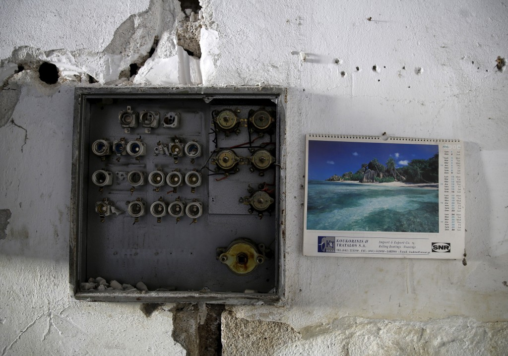 A calendar from the year 2000 is seen next to a destroyed electricity panel inside a cotton spinning factory in the town of Larissa in Thessaly region, Greece April 22, 2015. Photo by Yannis Behrakis/Reuters