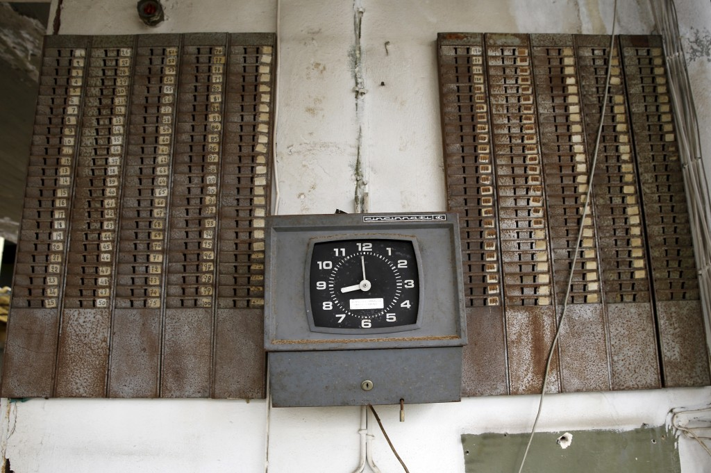 A punch clock is seen at the entrance of a deserted cooking oil factory that closed in 1996 in the town of Elefsina in Sterea Hellas region, Greece April 28, 2015. Photo by Yannis Behrakis/Reuters