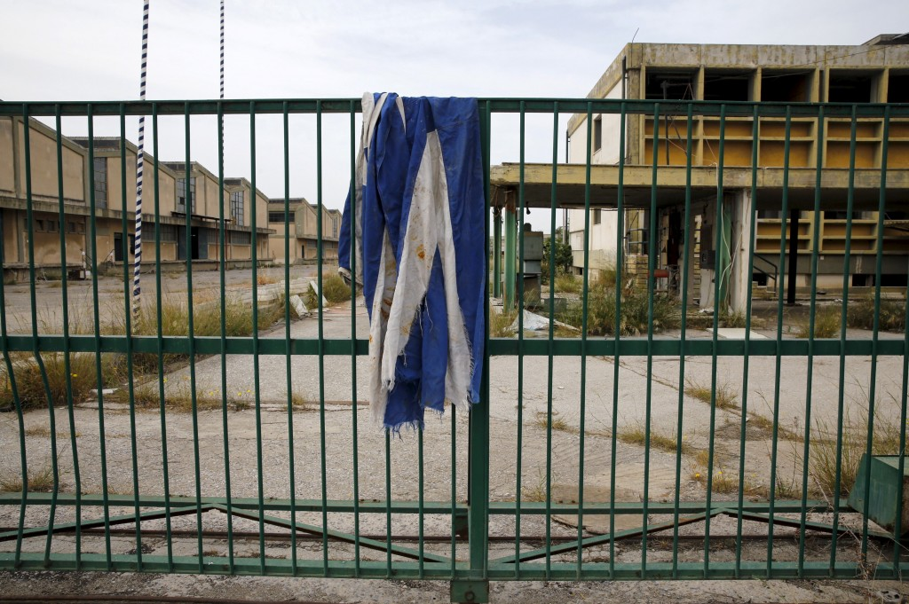 A Greek flag is draped over the gate of a deserted cooking oil factory that closed in 1996 in the town of Elefsina in Sterea Hellas region, Greece April 28, 2015. Photo by Yannis Behrakis/Reuters