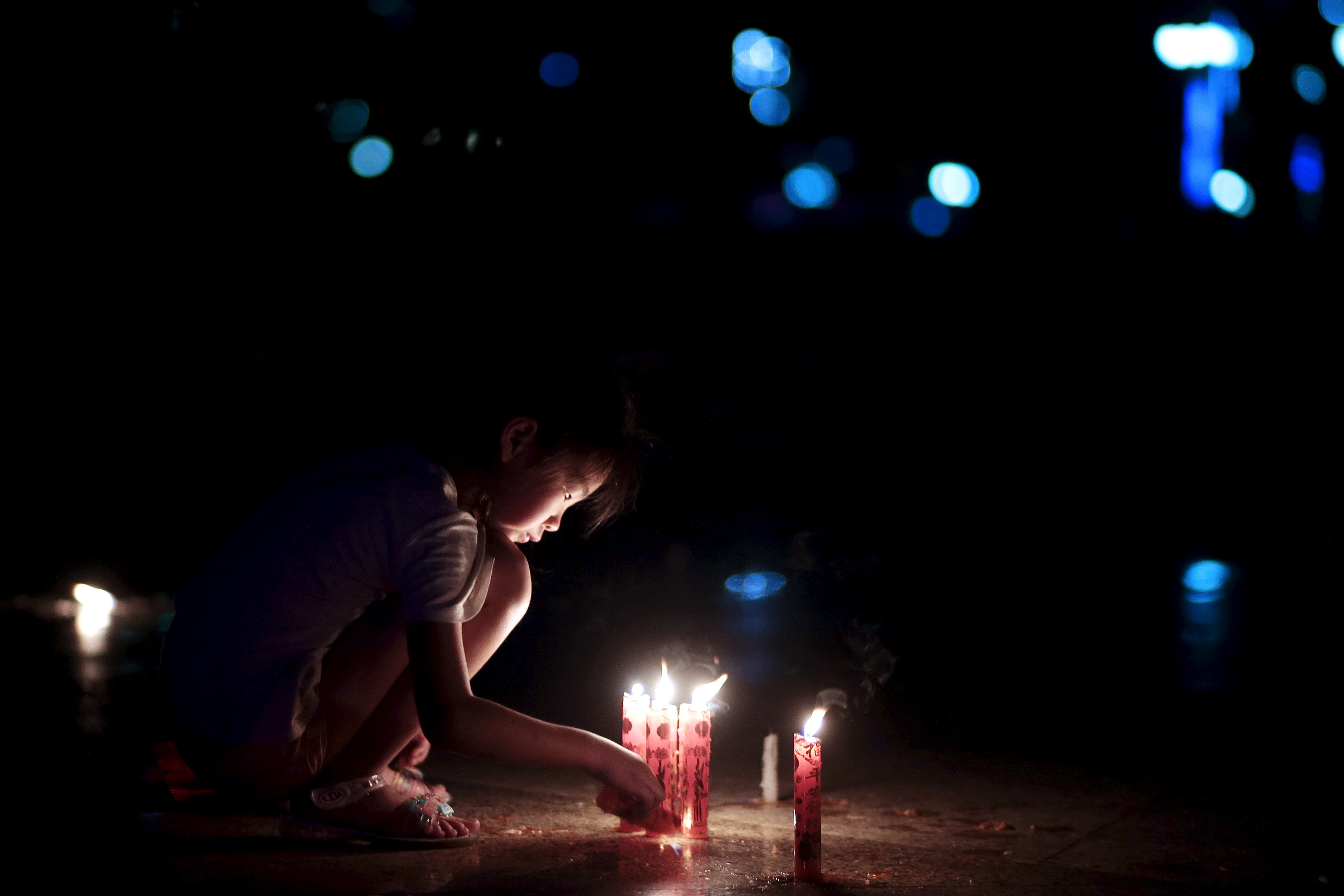 A girl lights a candle at a candlelight vigil to pay respect to the passengers of the sunken cruise ship Eastern Star on the Yangtze River, at a public square in Jianli, Hubei province, China, June 5, 2015. Aly Song/Reuters