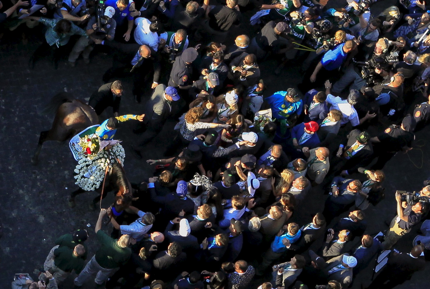 Espinoza, sitting atop American Pharoah, waves to fans from the winners circle after winning the Belmont Stakes. Photo by Carlo Allegri /Reuters