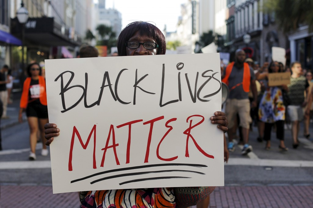 "Louise Brown walks in the ""March for Black Lives"" after passing by the Emanuel African Methodist Episcopal Church in Charleston, South Carolina June 20, 2015 three days after a mass shooting left people nine dead during a bible study at the church.     REUTERS/Brian Snyder - RTX1HEVI"