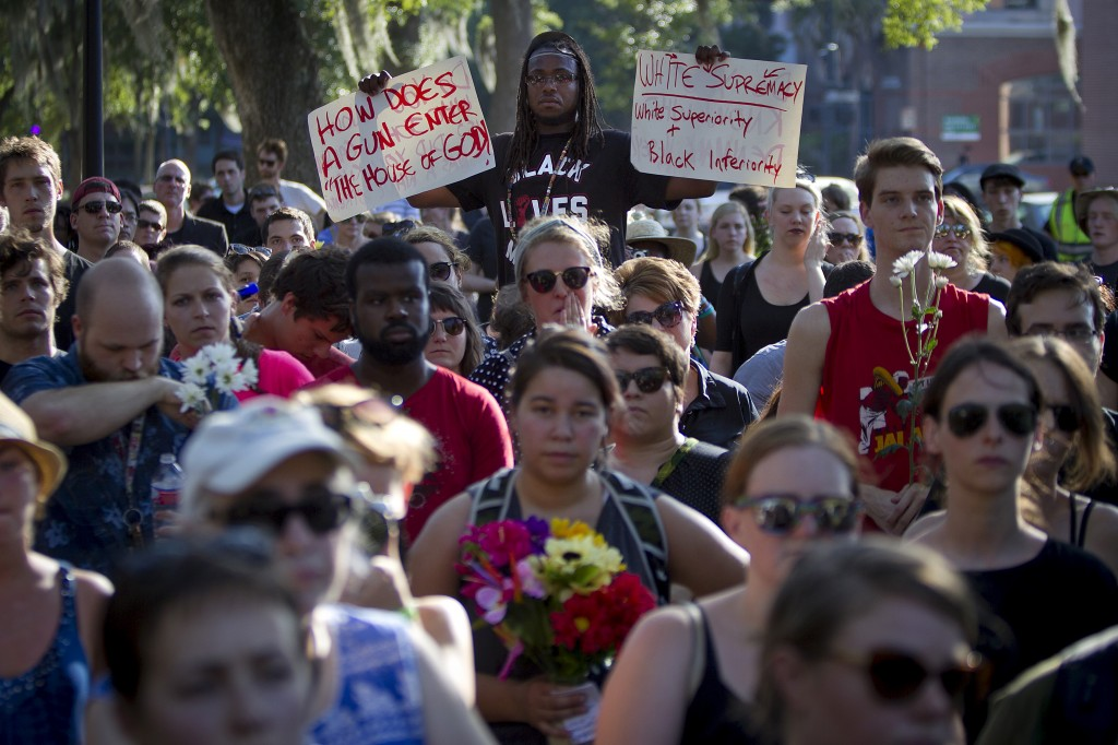 "People take part in ""Black Lives Matter"" march around Emanuel African Methodist Episcopal Church in Charleston, June 20, 2015. Dylann Roof, a 21-year-old with a criminal record, is accused of killing nine people at a Bible-study meeting in the historic African-American church in Charleston, South Carolina, in an attack U.S. officials are investigating as a hate crime.      REUTERS/Carlo Allegri - RTX1HF0K"