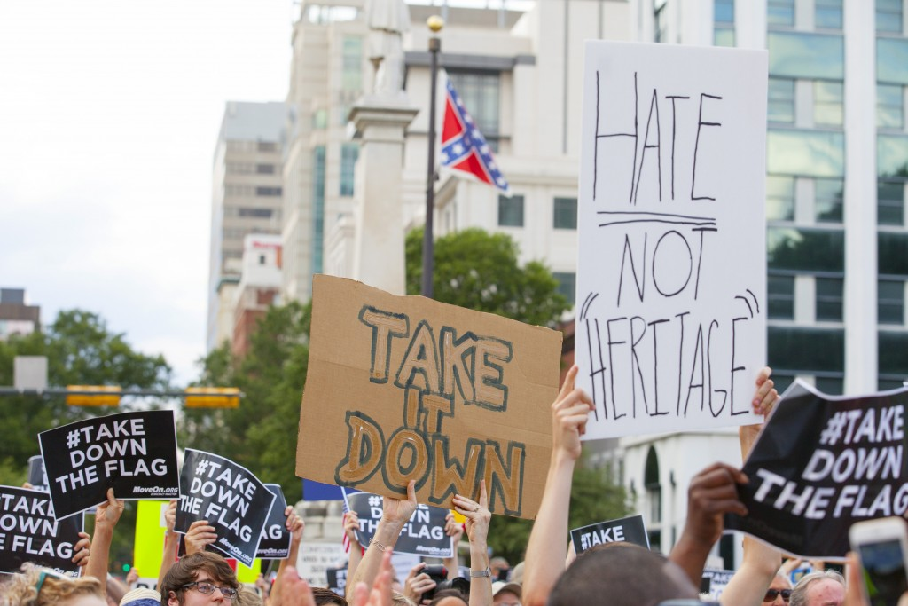 People hold signs during a protest asking for the removal of the confederate battle flag that flies at the South Carolina State House in Columbia, SC June 20, 2015.  REUTERS/Jason Miczek      TPX IMAGES OF THE DAY      - RTX1HFBL