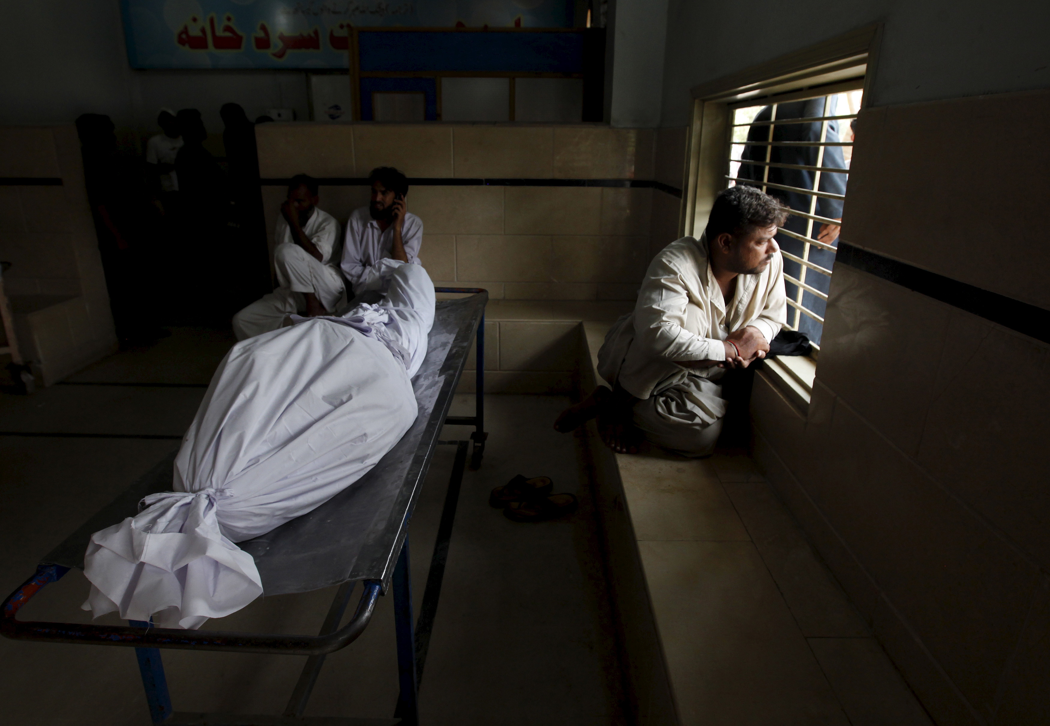 Relatives sit beside the body of someone who died due to an intense heat wave in Karachi, Pakistan on June 22. Photo by Akhtar Soomro/Reuters
