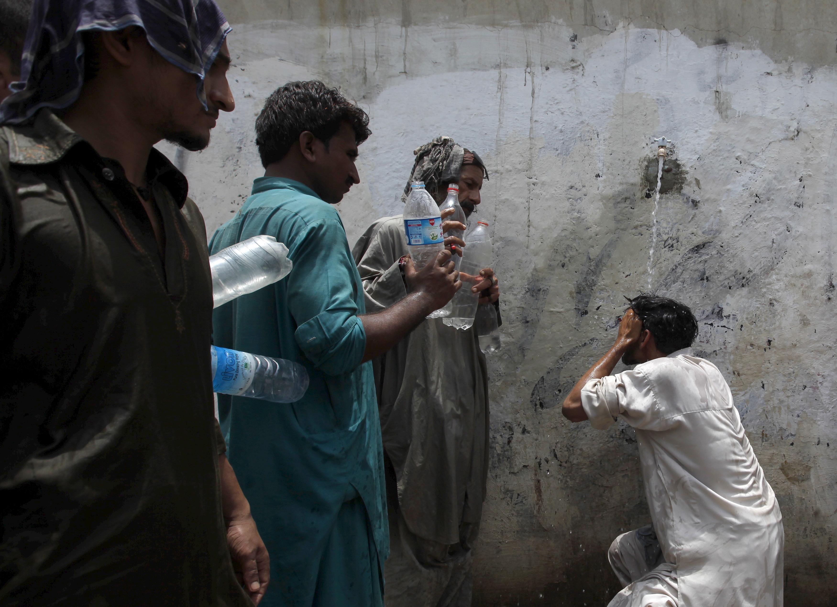 Men fill their water bottles at a public tap in Karachi, Pakistan on June 23, following days of intense heat. Photo by Akhtar Soomro/Reuters