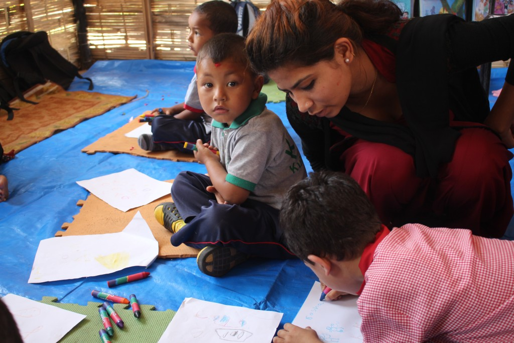 A facilitator helps children at a UNICEF-supported temporary learning center at Kuleshwor Awas Secondary School in Nepal's capital Kathmandu on May 31. Photo courtesy of UNICEF