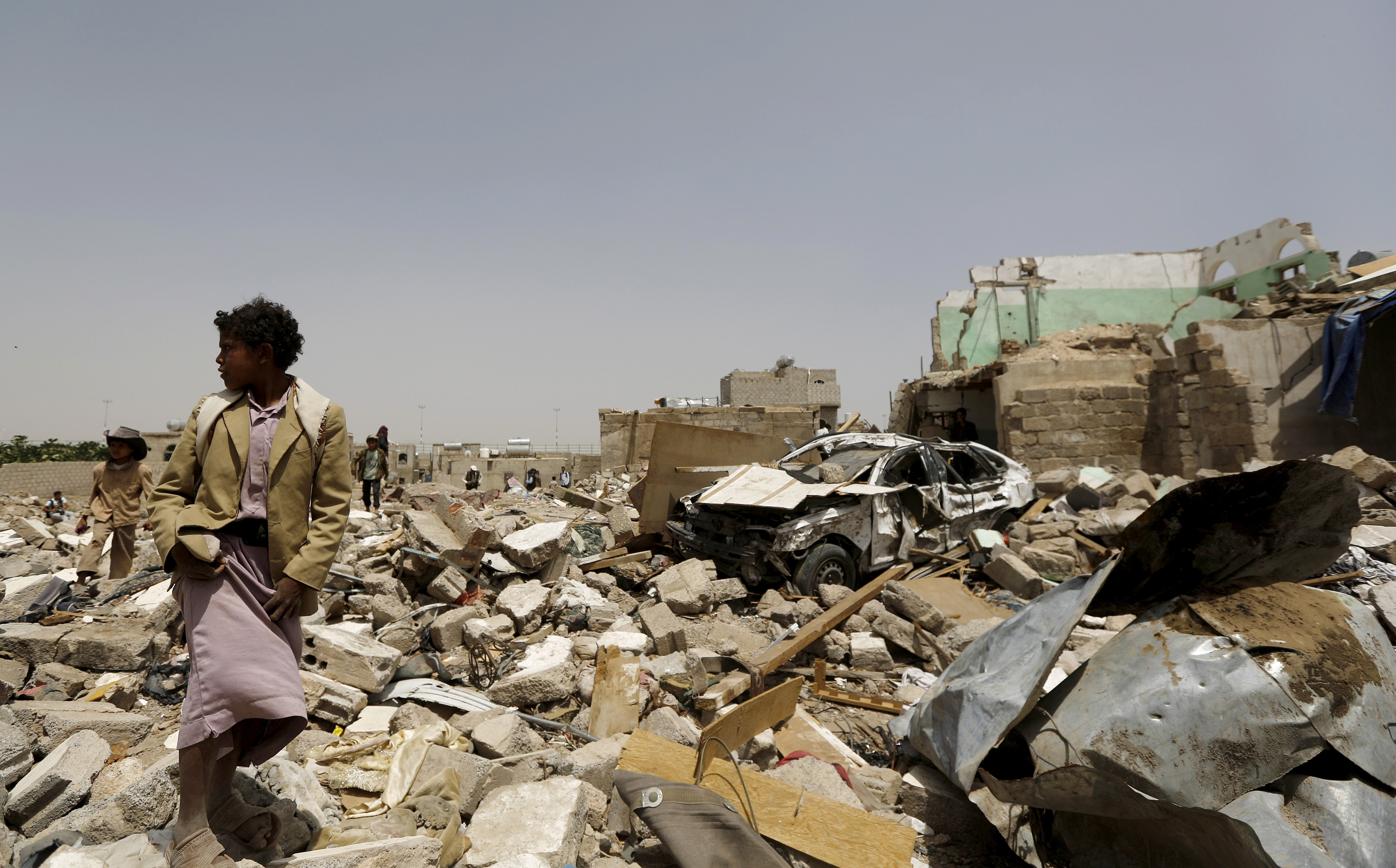 A boy walks at the site of a Saudi-led air strike that hit a residential areanear Sanaa airport, on May 18, 2015. Photo by Khaled Abdullah/Reuters