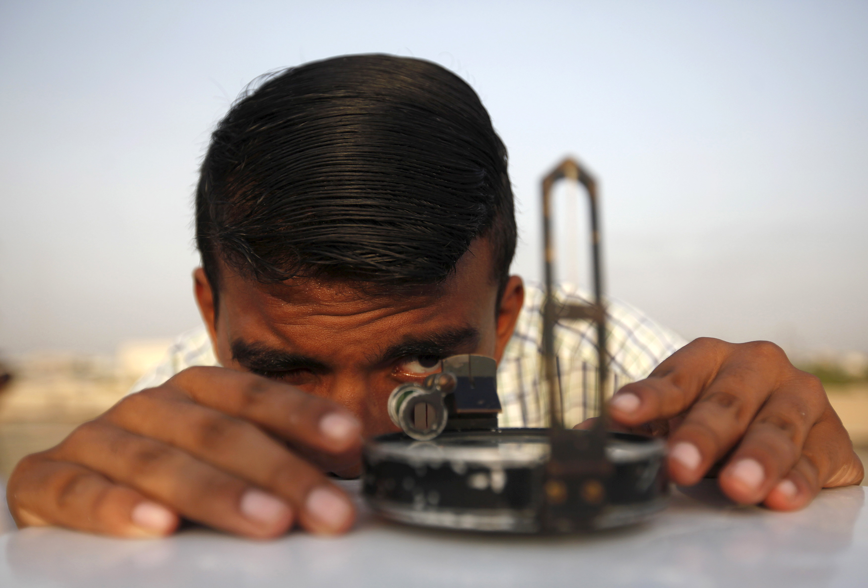 A man adjusts his compass to find the proper direction before installing a theodolite to look for the new moon that will mark the start of Ramadan in Karachi, Pakistan on June 17, 2015. Photo by Akhtar Soomro/Reuters