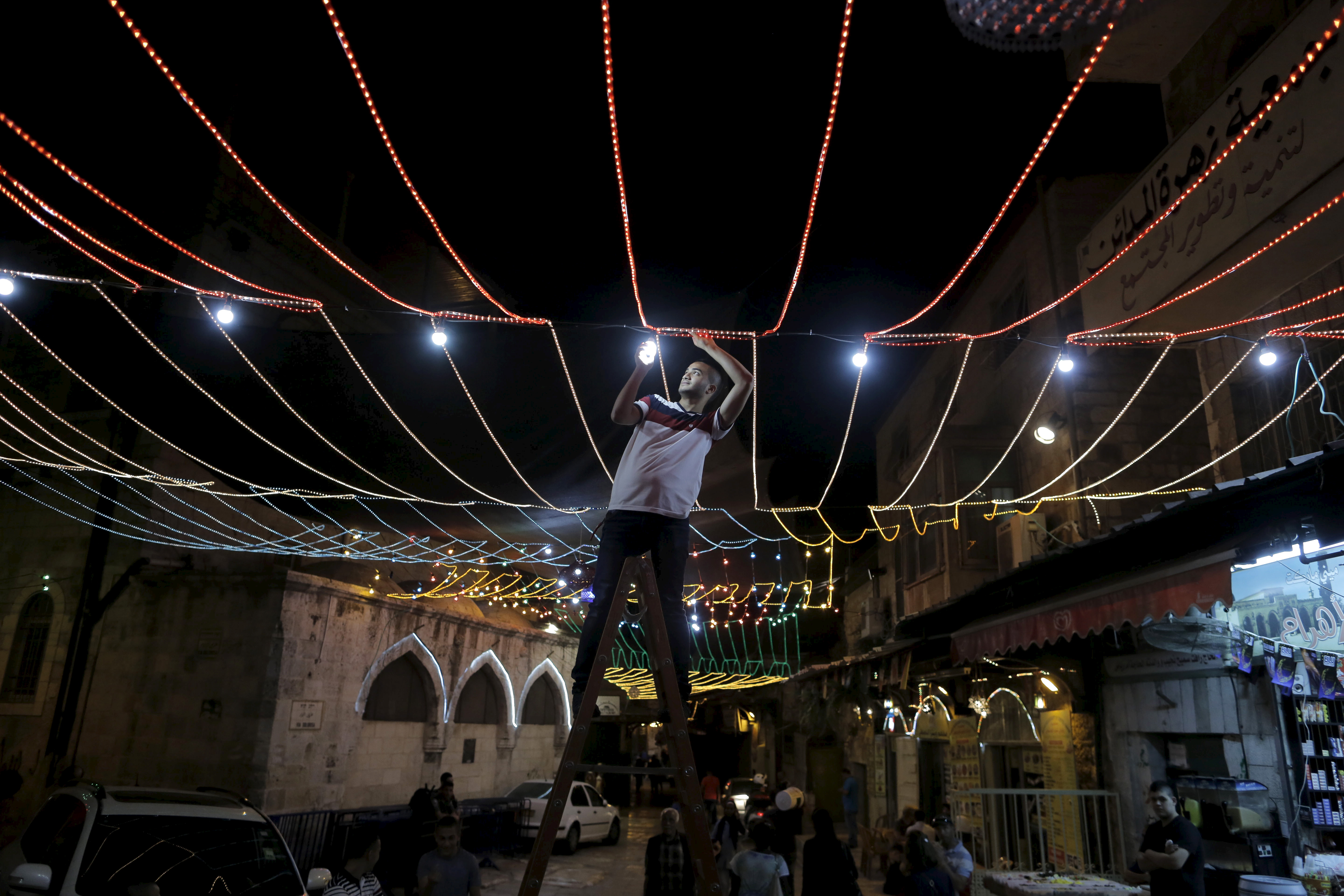 A Palestinian man hangs decorations for the upcoming holy month of Ramadan outside his home in Jerusalem's Old City on June 16, 2015.  Photo by Ammar Awad/Reuters