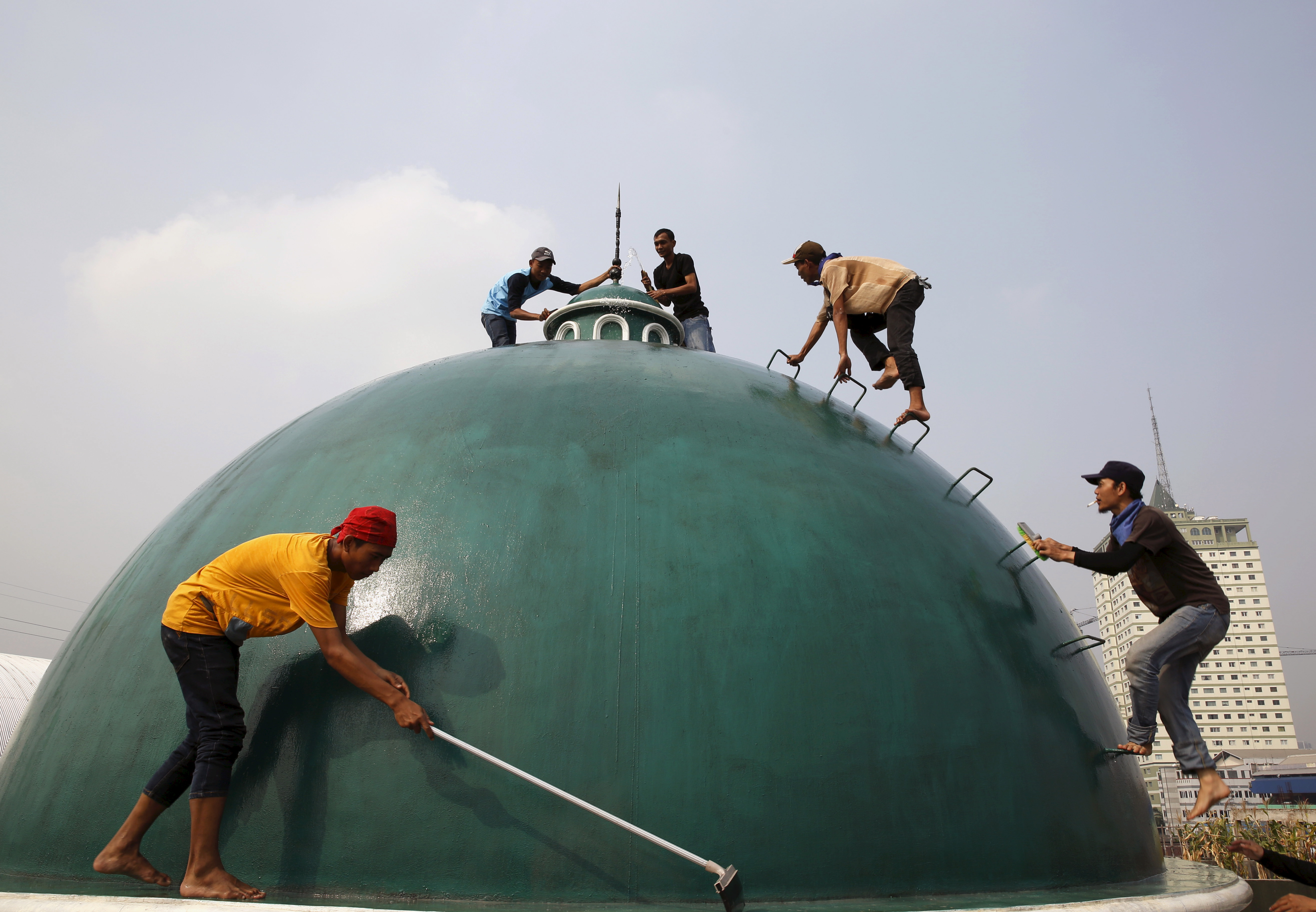 Youths clean the dome of a mosque ahead  of Ramadan in Jakarta, Indonesia on June 15, 2015. Photo by Beawiharta/Reuters