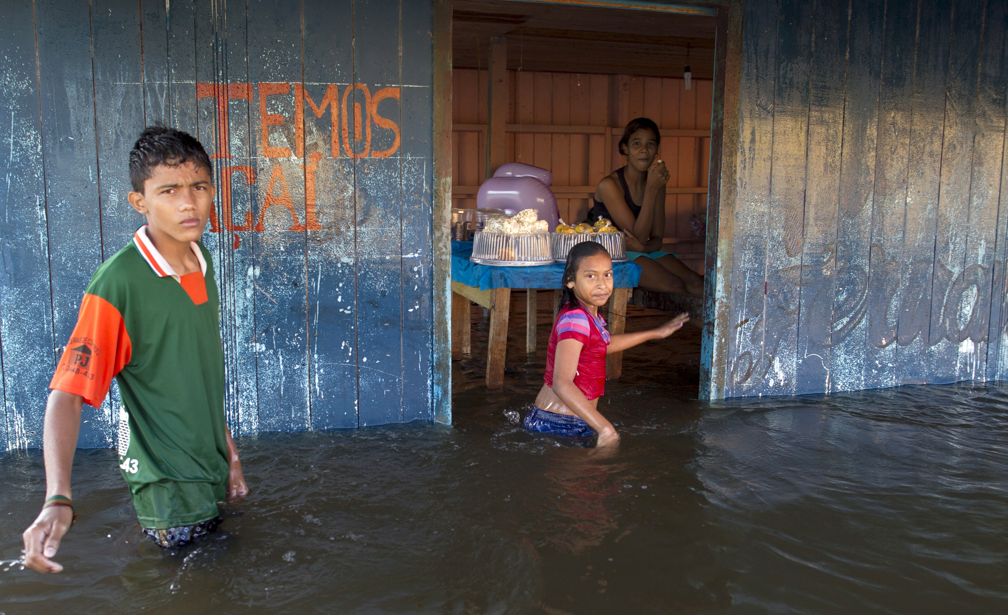 Children walk in front of a small bar in a street flooded by the rising Rio Solimoes, one of the two main branches of the Amazon River, in Anama, Amazonas state, Brazil on June 3, 2015. Photo by Bruno Kelly/Reuters