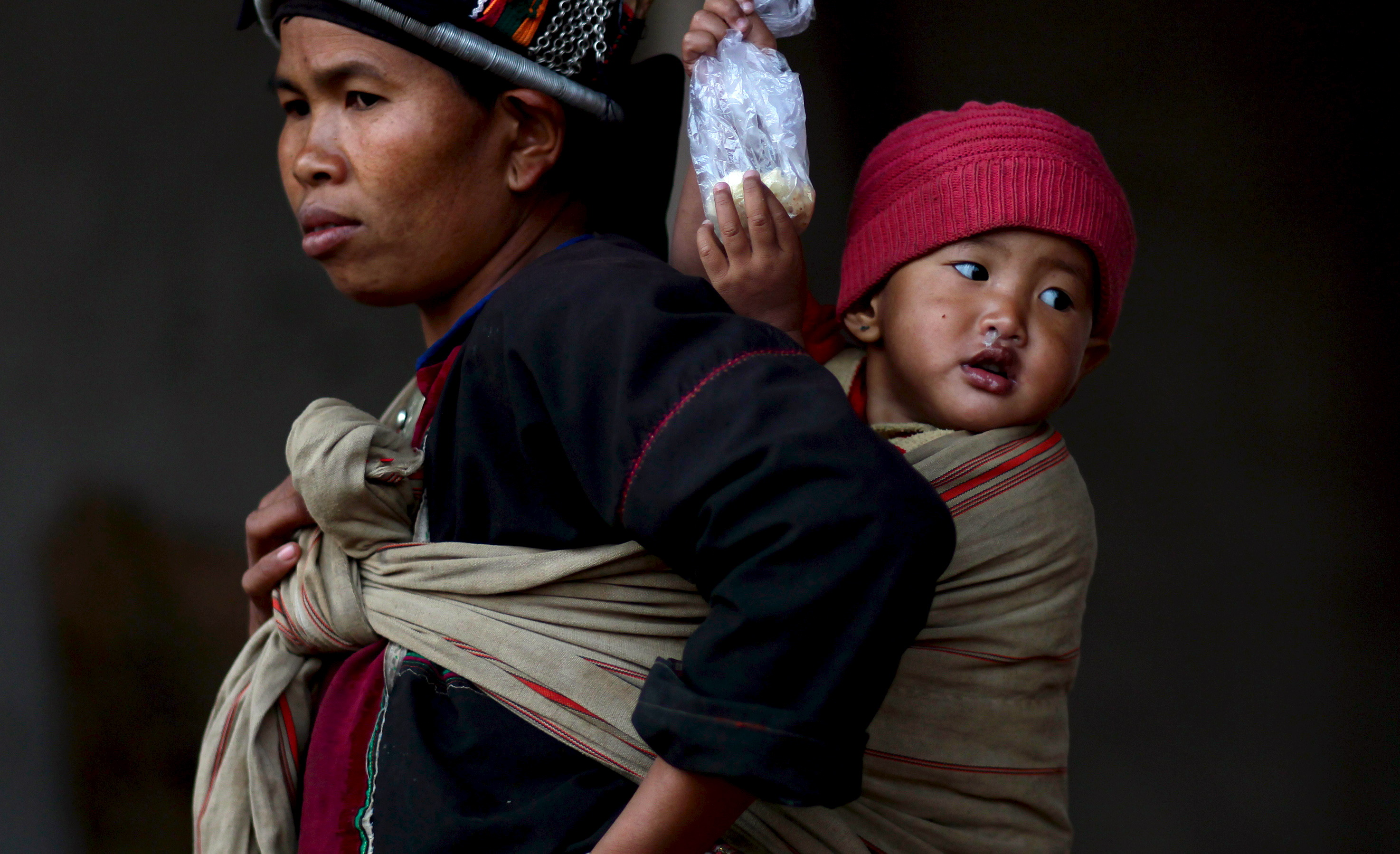 A woman carries her baby at a refugee camp in Kokang at Myanmar's border with China, on March 24, 2015. Photo by Wong Campion/Reuters