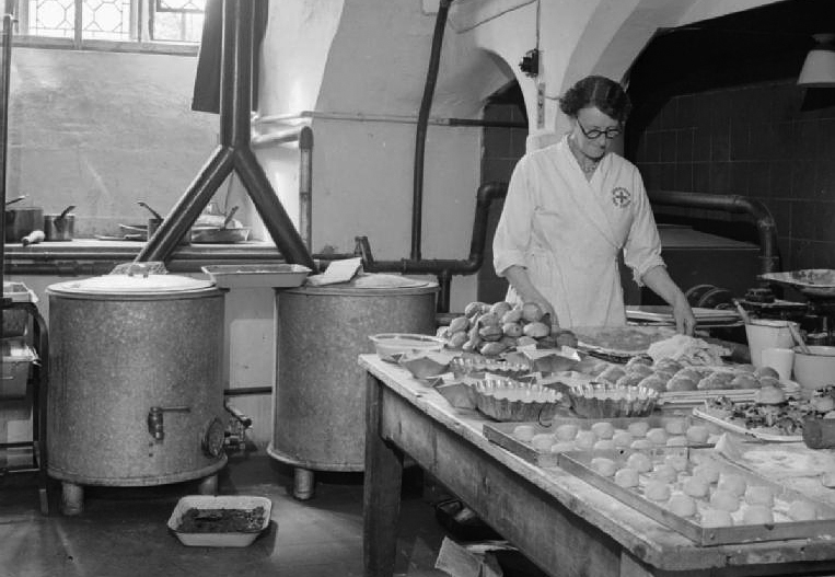 "In the 600 year old vaulted kitchen of the American Red Cross Service Club at the Bishop's Palace in Norwich, Mrs Babstock the cook sets out doughnuts, cakes and pastries on trays, ready to serve to the hungry American service personnel staying at the Club. Prior to working at the Club, Mrs Babstock was the supervisor of the British Restaurant in Warwick. According to the original caption, the British have ""provided modern gas cookers, hot plates, washing machines, dough mixers, waffle machines, and a first class kitchen staff"" as part of the Reciprocal Aid Agreement."