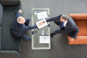 Businessmen shaking hands across coffee table in lobby. Photo by Getty Images.