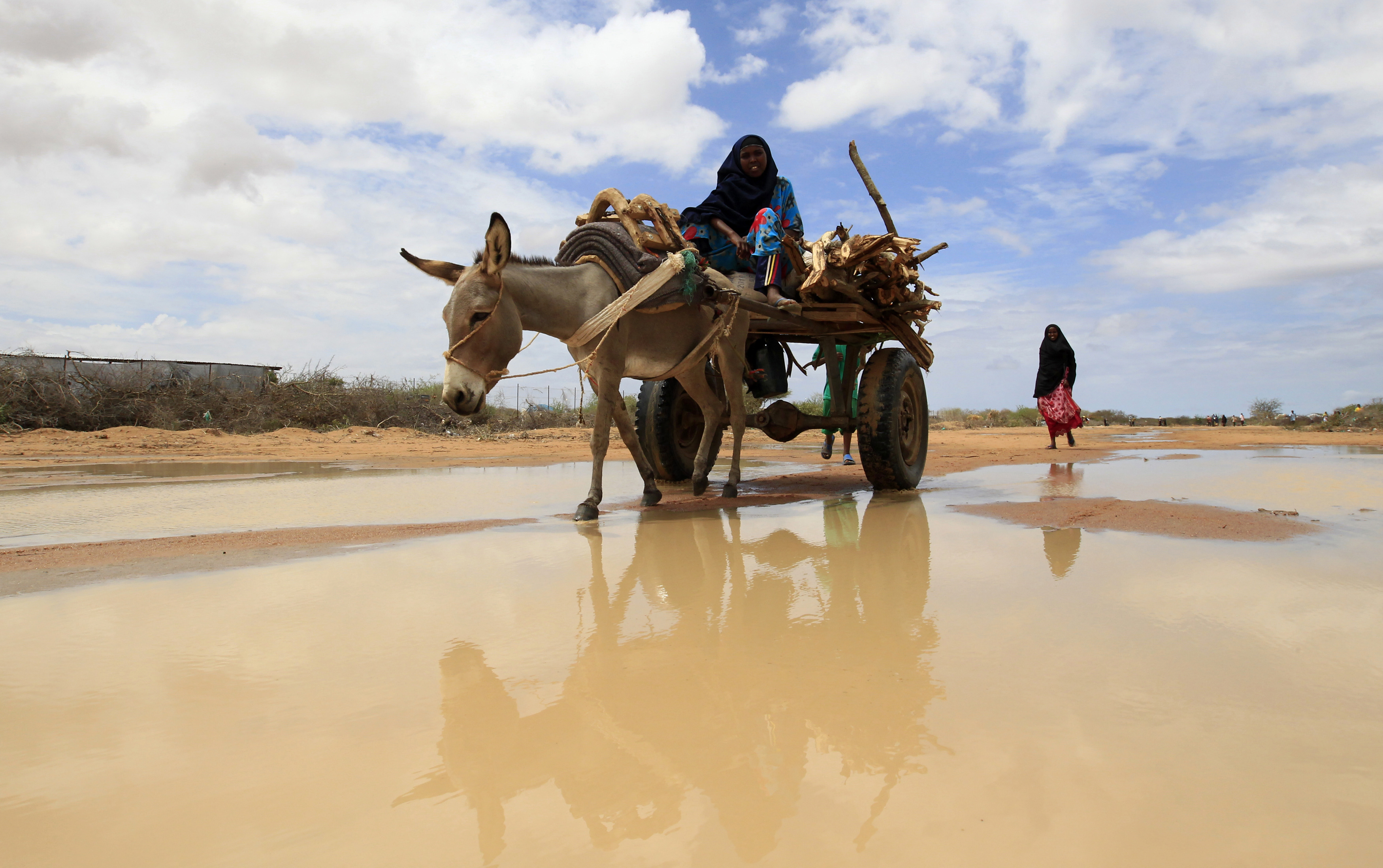 A woman rides her donkey along a flooded street at the Ifo extension refugee camp in Dadaab. Photo by Thomas Mukoya/Reuters