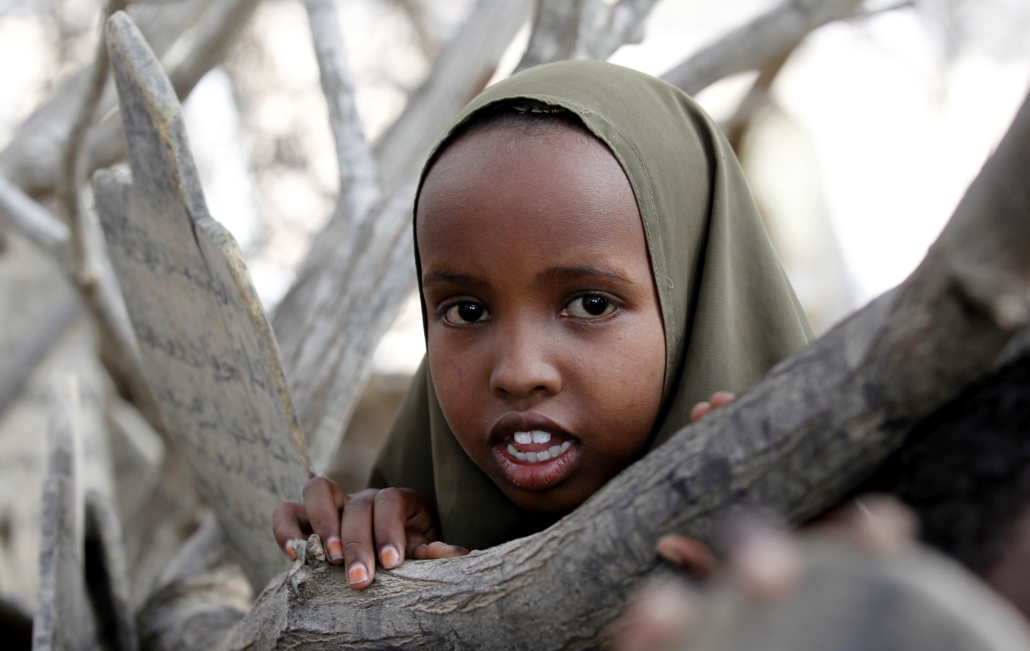 A refugee student stands inside a makeshift madrasa, or Islamic school, under a tree at the Ifo 2 east camp within the Dadaab refugee complex. Photo by Thomas Mukoya/Reuters