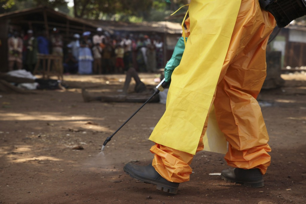 A member of the French Red Cross disinfects the area around a person suspected of carrying the Ebola virus in Forecariah in southwestern Guinea on Jan. 30.  Photo by Misha Hussain/Reuters