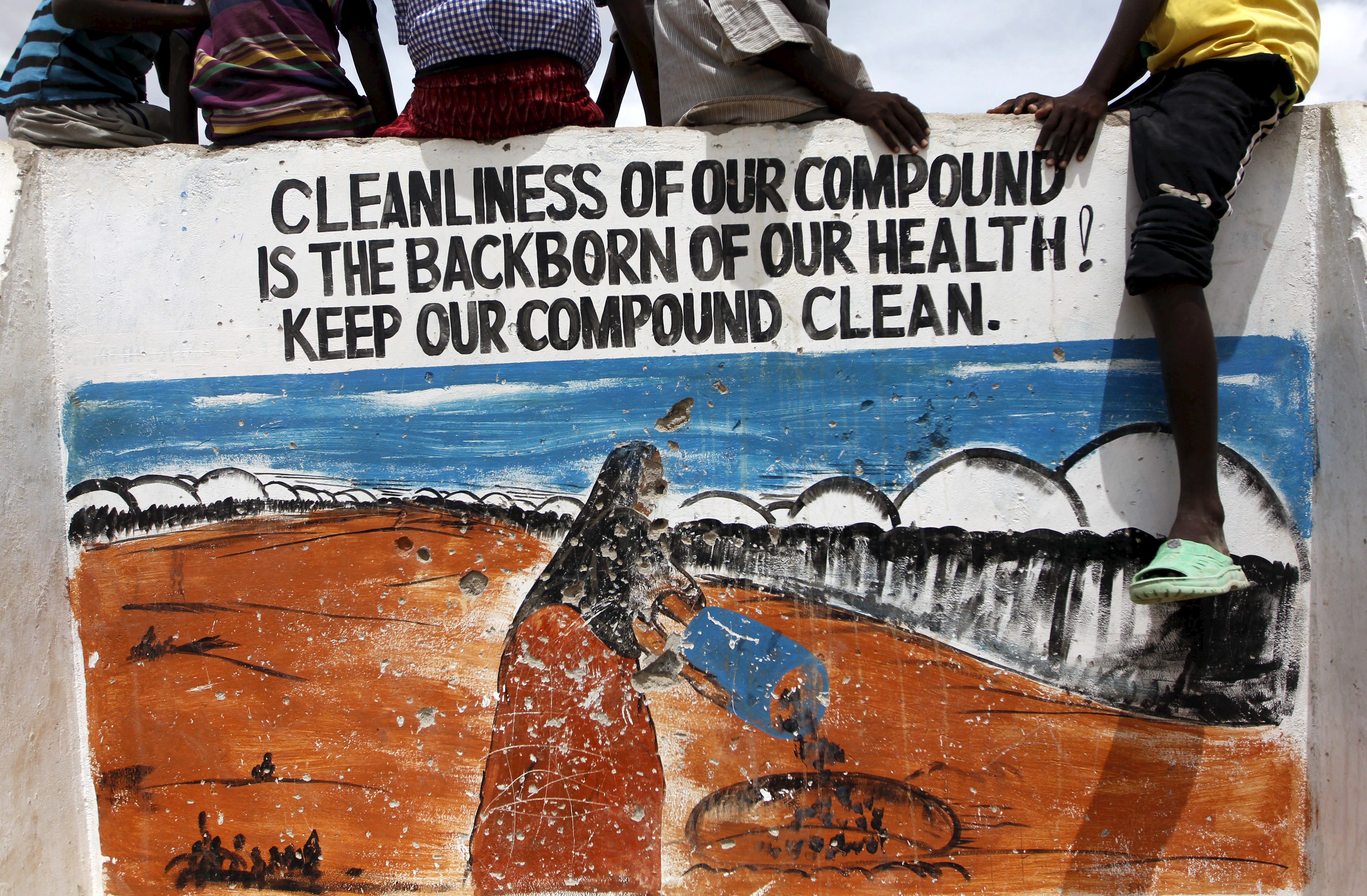Refugees sit on a wall with a mural on hygiene at the Ifo camp in Dadaab near the Kenya-Somalia border on May 8, 2015. Photo by Thomas Mukoya/Reuters
