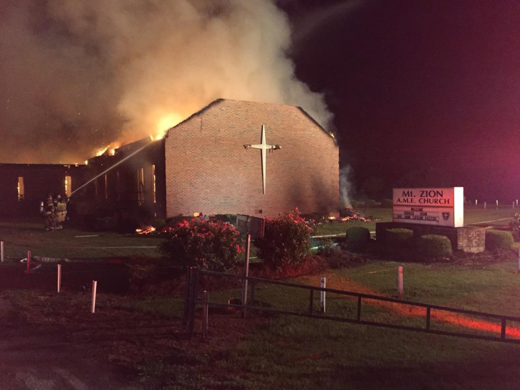 Fire crews try to control a blaze at the Mt. Zion African Methodist Episcopal Church in Greeleyville, South Carolina in this June 30, 2015 handout photo. The cause was not immediately clear. The fire comes amid a rash of fires that have erupted at black churches across the U.S. south, at least two of which have already been declared as deliberate. Photo by Clarendon County Fire Department/Handout via Reuters