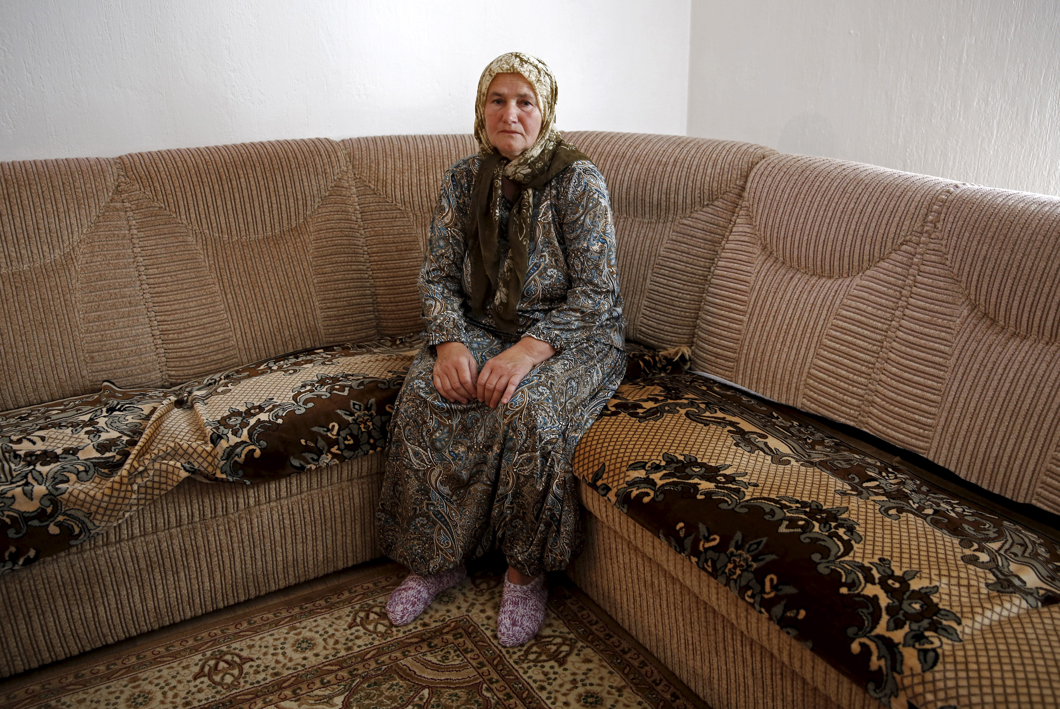 "Nura Sulic poses for a picture in her home in Zivinice, Bosnia and Herzegovina, July 1, 2015. Nura is among several thousand women still searching for the remains of their closest relatives 20 years after the Srebrenica massacre of 8,000 Muslim men and boys. Nura Sulic, is still searching for her son. She lost 11 close family members. ""His photograph is all I have left of him. I pray to dear Allah to find at least one, smallest bone. Anything. So that we would both finally be at peace.""  Picture taken on July 1, 2015. REUTERS/Dado Ruvi - RTX1IUDT"