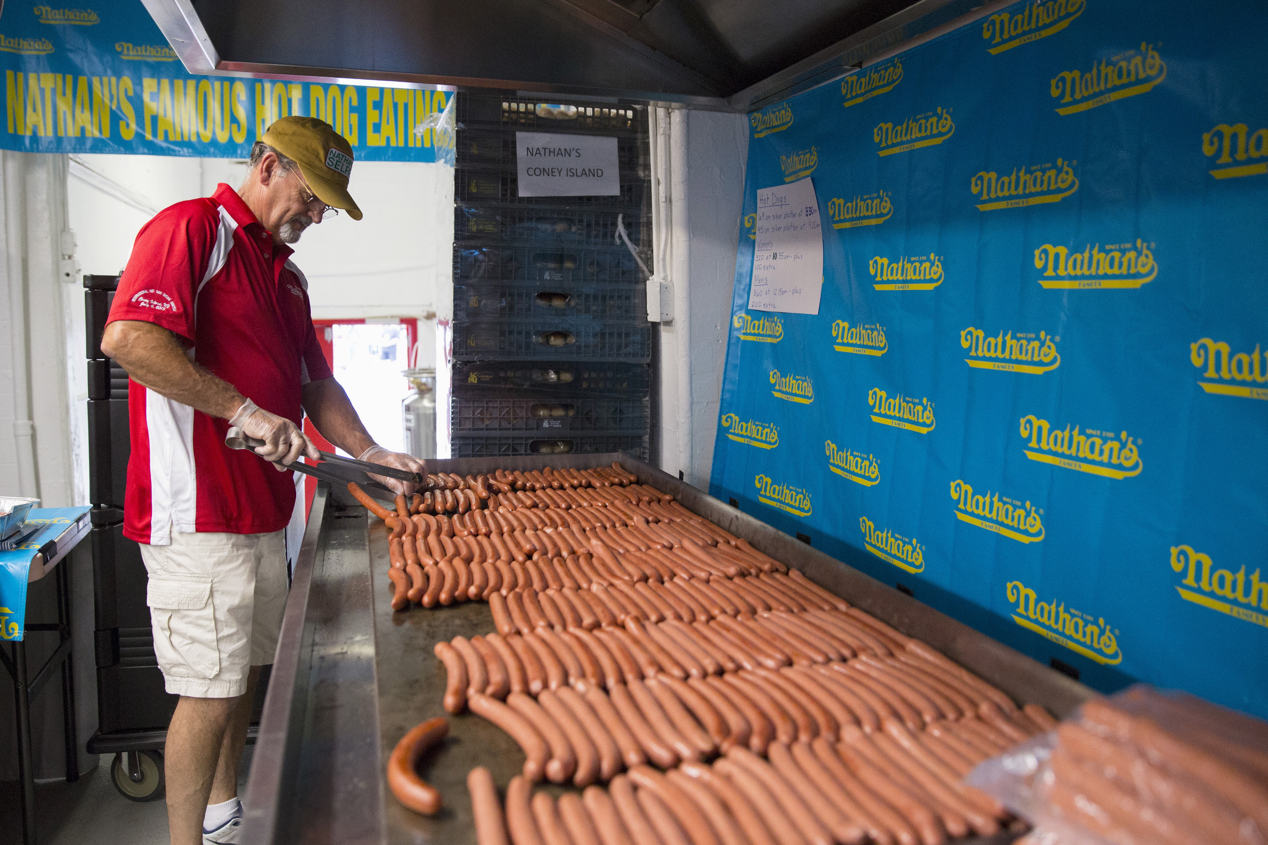 Kevin McDonald of Jackson, New Jersey prepares sausages for Nathan's Famous Hot Dog Eating Contest in Brooklyn, New York July 4, 2015. McDonald has been cooking the sausages for the contest since 1997 and averages 2,600 sausages cooked per year. REUTERS/Andrew Kelly - RTX1IZYL