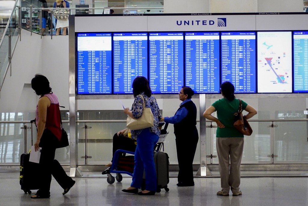 People look at the United Airlines timetable in Newark International Airport, New Jersey July 8, 2015. United Airlines resumed flights at all U.S. airports on Wednesday after they were grounded due to computer issues, according to the Federal Aviation Administration.  The FAA issued the order to prevent all United Airlines flights from taking off following a systemwide computer glitch, which was resolved, the agency said. REUTERS/Eduardo Munoz - RTX1JKUJ