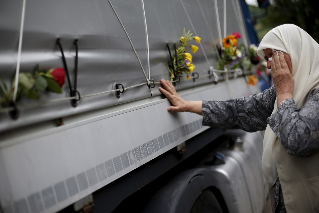 A woman reacts as she touches a truck carrying 136 coffins of newly identified victims of the 1995 Srebrenica massacre, in the village of Visoko July 9, 2015. The bodies of the 136 recently identified victims of Srebrenica massacre will be transported to the memorial centre in Potocari where they will be buried on July 11, the anniversary of the massacre when Bosnian Serb forces slaughtered 8,000 Muslim men and boys and buried them in mass graves in Europe's worst massacre since World War Two.  REUTERS/Stoyan Nenov       TPX IMAGES OF THE DAY      - RTX1JNXV