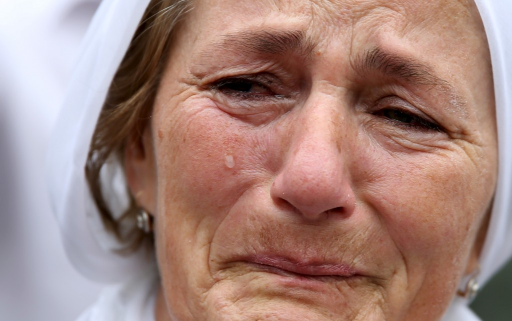 A woman cries near a truck carrying 136 coffins of newly identified victims of the 1995 Srebrenica massacre, in front of the presidential building in Sarajevo July 9, 2015. The bodies of the 136 recently identified victims of Srebrenica massacre will be transported to the memorial centre in Potocari where they will be buried on July 11, the anniversary of the massacre when Bosnian Serb forces slaughtered 8,000 Muslim men and boys and buried them in mass graves in Europe's worst massacre since World War Two. REUTERS/Dado Ruvic - RTX1JOXN