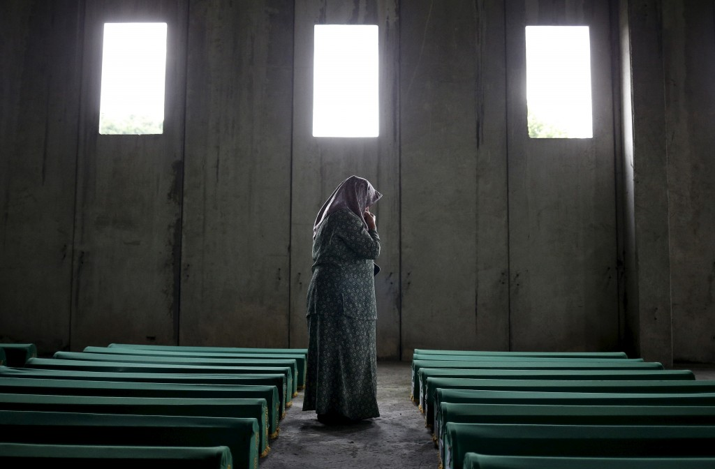 A woman searches for her relative's name on the coffins of newly identified victims of the 1995 Srebrenica massacre, at the Memorial Center in Potocari near Srebrenica, Bosnia and Herzegovina, July 9, 2015. The bodies of the 136 recently identified victims of Srebrenica massacre will be buried on July 11, the anniversary of the massacre when Bosnian Serb forces slaughtered 8,000 Muslim men and boys and buried them in mass graves in Europe's worst massacre since World War Two.  REUTERS/Stoyan Nenov  - RTX1JQXL