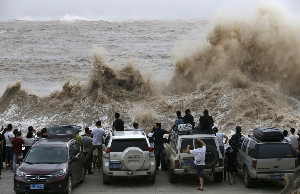 People look on as waves from Typhoon Chan-hom hit the shore in Wenling, Zhejiang province in China on July 10, 2015. Typhoon warnings have been distributed across almost all coastal cities in east China as Typhoon Chan-hom affects areas between Shanghai, Fujian province, and Taiwan. Photo by William Hong/Reuters