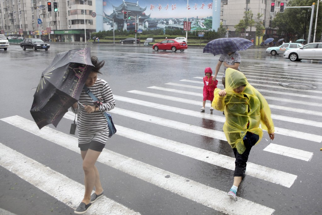 Pedestrians hold their umbrellas against strong winds as Typhoon Chan-Hom hits Shanghai, China, July 11, 2015. Treacherous rain and harsh winds have forced highways, railways, and airports to cancel services. Photo by Stringer/Reuters