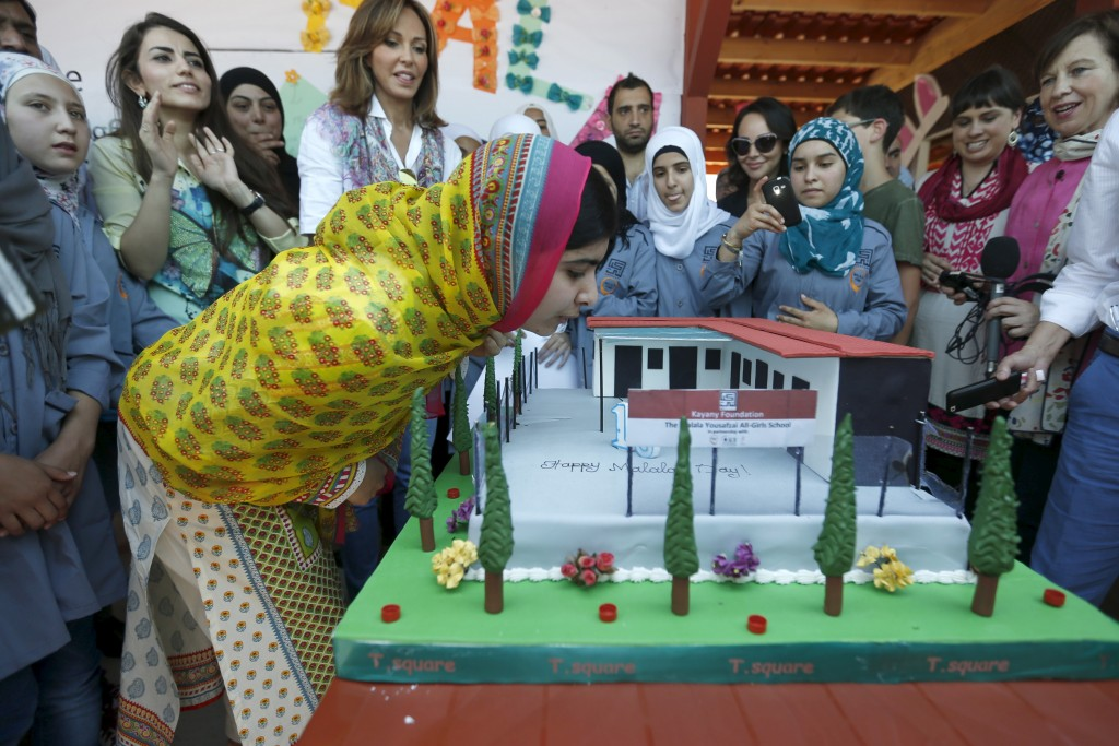 "Nobel Peace Prize laureate Malala Yousafzai (C) blows out candles on her birthday cake at a school for Syrian refugee girls, built by the NGO Kayany Foundation, in Lebanon's Bekaa Valley July 12, 2015. Yousafzai celebrated her 18th birthday in Lebanon on Sunday by opening the school and called on world leaders to invest in ""books not bullets"". The Malala Fund, a non-profit organisation that supports local education projects, paid for the school. Noura Jumblatt , Kayany Founder and wife of Lebanon's Druze leader Walid Jumblatt is seen behind her. Photo by Jamal Saidi/Reuters"