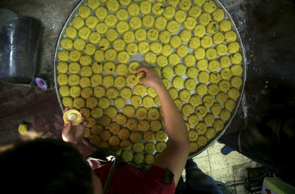 A Palestinian prepares traditional cake at a sweets shop in preparation for Eid al-Fitr in the West Bank city of Nablus on July 15, 2015. Photo by Abed Omar Qusini/Reuters