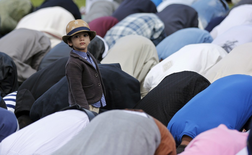 A young muslim boy stands up as Muslim men perform prayers for Eid-al Fitr to mark the end of the holy fasting month of Ramadan at a park in London, Britain on July 17, 2015. Photo by Suzanne Plunkett