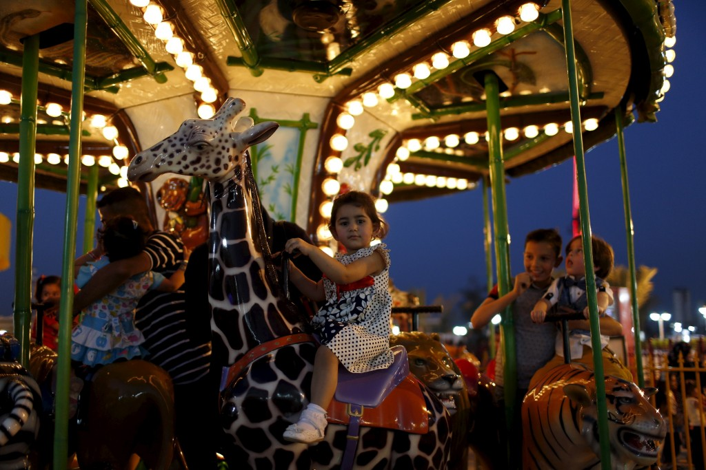 A child enjoys a ride in an amusement park during Eid al-Fitr celebrations in Baghdad on July 17, 2015. Photo by Thaier al-Sudani/Reuters