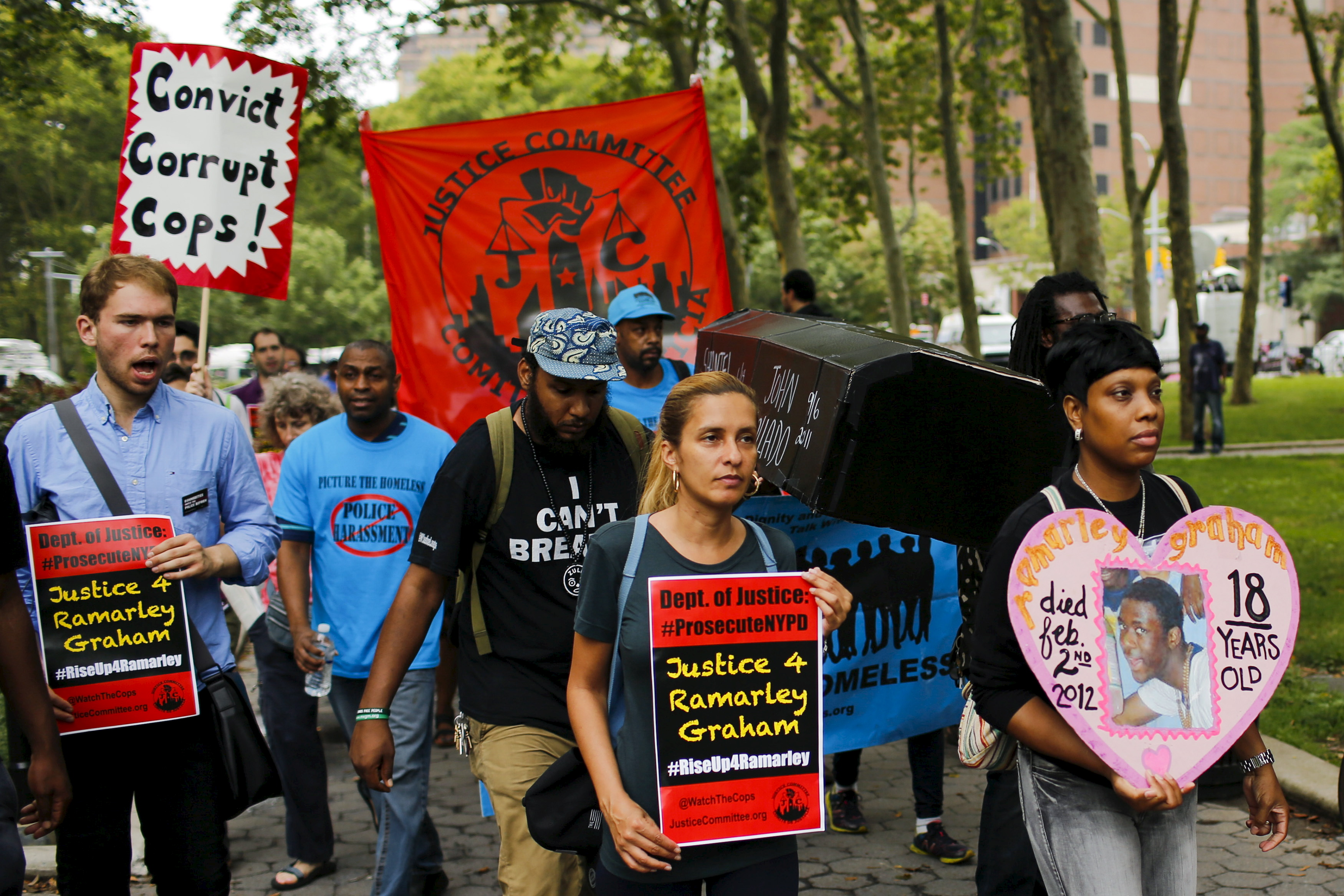Protesters carry symbolic caskets of people killed by police during a rally for Eric Garner near a Brooklyn court in New York, July 18, 2015. Family and supporters marked the anniversary of the police killing of Eric Garner with rallies and vigils demanding police reforms and justice in the controversial case. Photo by Eduardo Munoz/Reuters