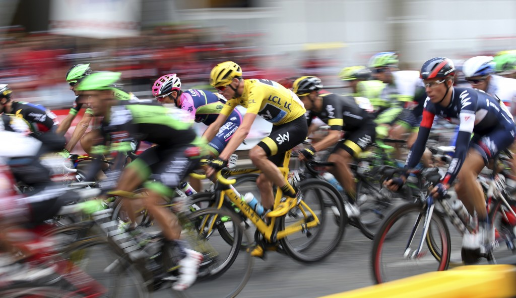 Team Sky rider Chris Froome of Britain (C), the race leader's yellow jersey, cycles on the Champs-Elysees avenue during the 109.5-km (68 miles) final 21st stage of the 102nd Tour de France cycling race from Sevres to Paris Champs-Elysees, France on July 26, 2015. Participants at various stages of the race have spit on and booed Froome. Photo by Stefano Rellandini/Reuters