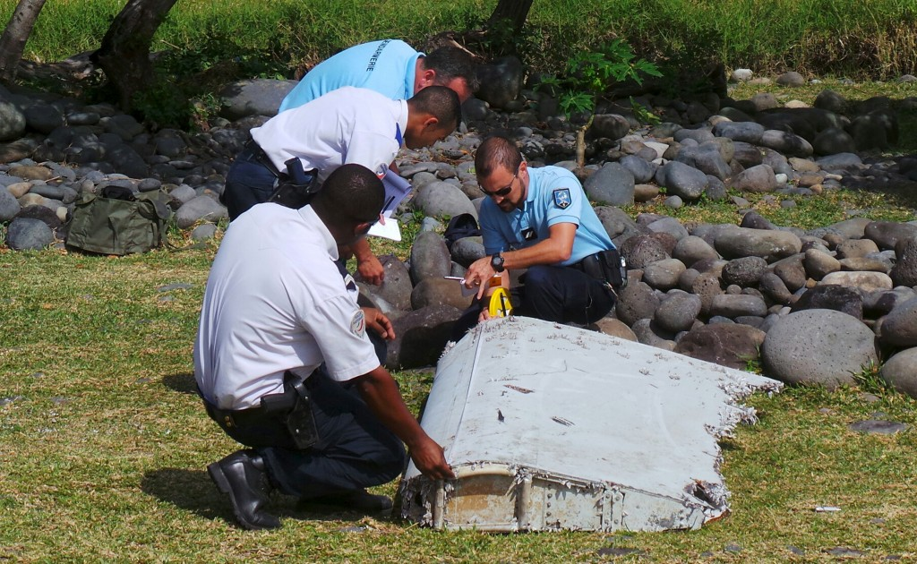 French gendarmes and police inspect a large piece of plane debris which was found on the beach in Saint-Andre, on the French Indian Ocean island of La Reunion. Picture taken July 29, 2015. Photo by Prisca Bigot via Reuters