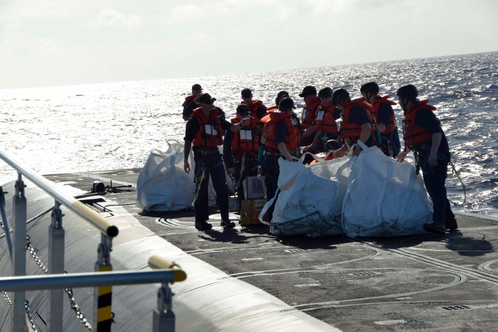 Sailors on the top side of the USS Pennsylvania dragging bags with food and supplies towards the submarine hatch. Photo by Dan Sagalyn
