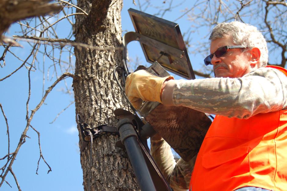 Eyes in the Woods volunteer John McGowan sets up a camera at Oak Creek Wildlife Area. Photo by Courtney Flatt/NWPR/EarthFix