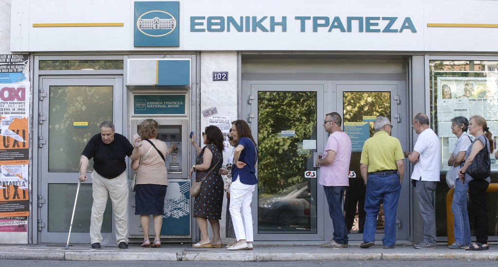 "Referendum campaign posters that read ""No"" in Greek are seen as people line up at an ATM outside a National Bank branch during a referendum vote in Athens, Greece, on July 5, 2015. Greece voted Sunday on whether to accept more austerity in exchange for international aid, in a high-stakes referendum likely to determine whether it leaves the eurozone after seven years of economic pain.   Photo by Christian Hartmann/Reuters  - RTX1J2LU"