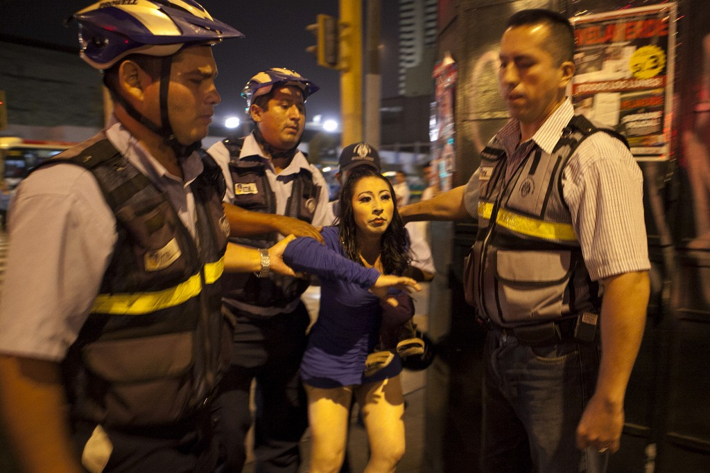 Though prostitution in Peru is not illegal, many transwomen are oftentimes taken by police on the basis of not being able to show their identification cards. Here, Kiara is taken by the municipal police officers, in a nightly raid. Photo and caption by Danielle Villasana