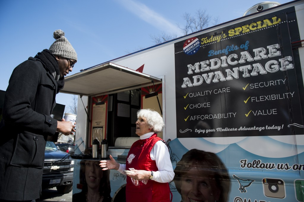 A woman speaks with pedestrians about the need for policymakers to protect Medicare Advantage benefits during the Coalition for Medicare Choices' Medicare Advantage Food Truck stop on North Capitol Street in Washington on Monday, March 9, 2015. Photo By Bill Clark/CQ Roll Call