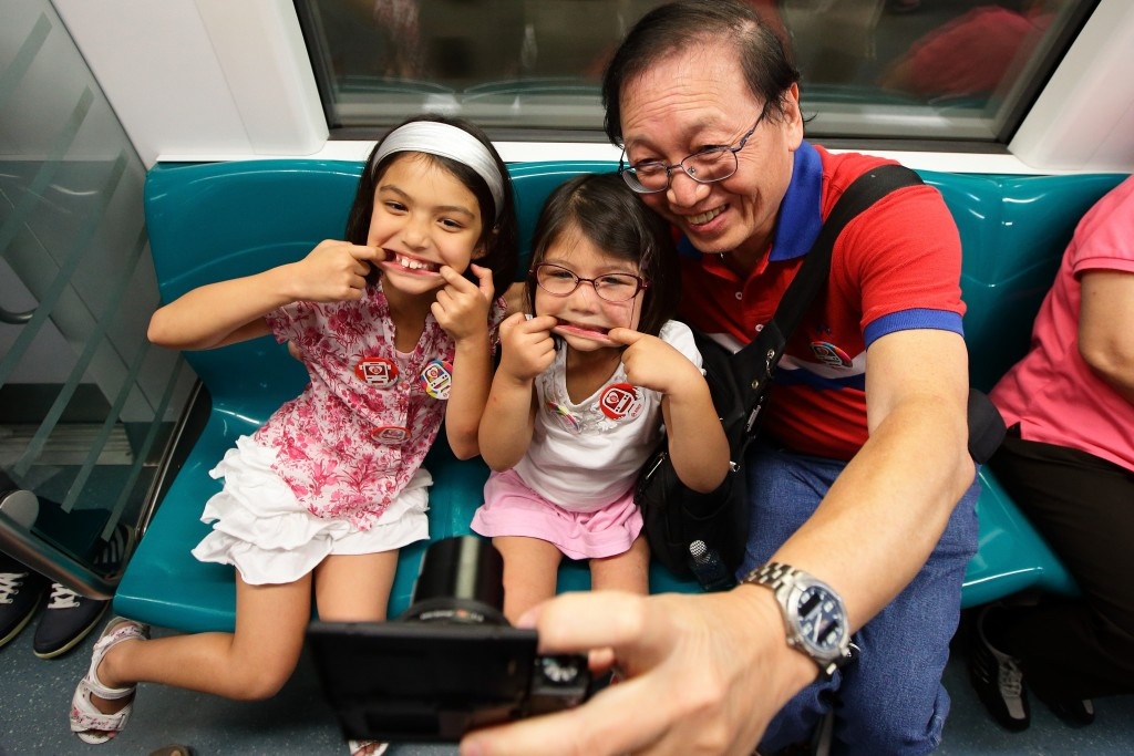 People enjoy free train ride for a day during the Singapore National Day on August 9, 2015 in Singapore. Photo by Suhaimi Abdullah/Getty Images.