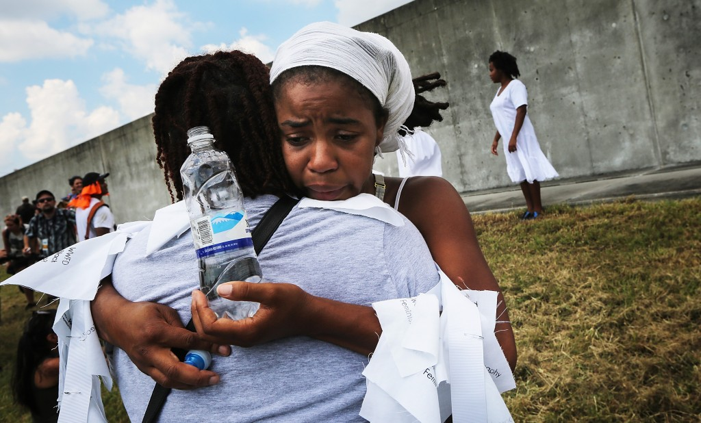 NEW ORLEANS, LA - AUGUST 29:  Women hug in front of the repaired levee wall in the Lower Ninth Ward on the 10th anniversary of Hurricane Katrina on August 29, 2015 in New Orleans, Louisiana.  A levee breach along the Industrial Canal in the Lower Ninth Ward devastated the area with massive flooding in the aftermath of Hurricane Katrina.  (Photo by Mario Tama/Getty Images)