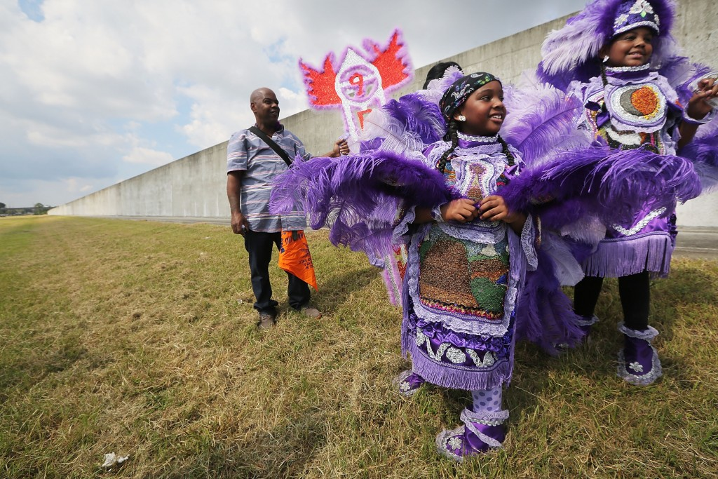 NEW ORLEANS, LA - AUGUST 29:  Kids are dressed in Mardi Gras Indian costumes along the repaired levee wall in the Lower Ninth Ward on the 10th anniversary of Hurricane Katrina on August 29, 2015 in New Orleans, Louisiana.  A levee breach along the Industrial Canal in the Lower Ninth Ward devastated the area with massive flooding in the aftermath of Hurricane Katrina.  (Photo by Mario Tama/Getty Images)