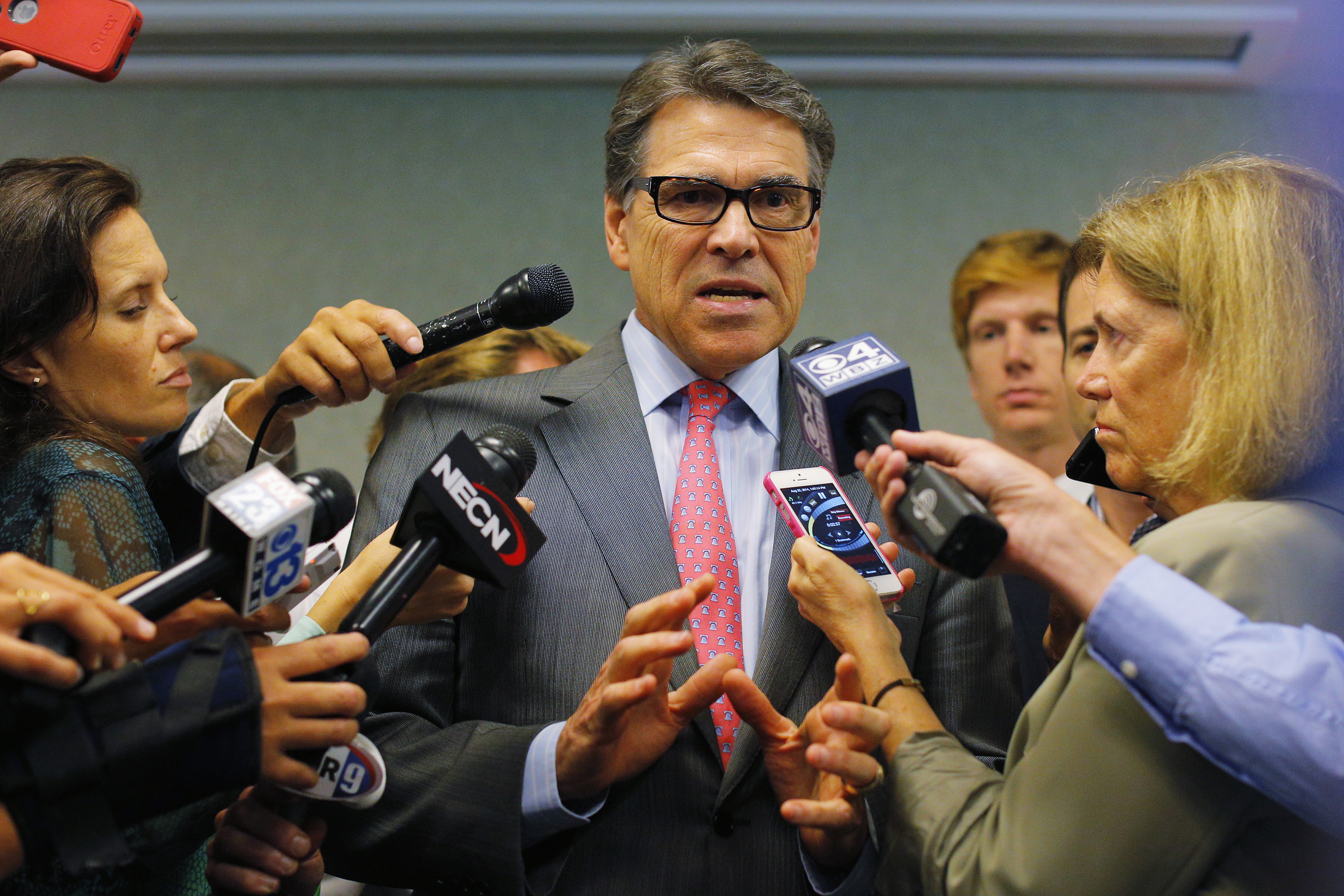 Texas Governor Rick Perry, a possible Republican candidate for the 2016 presidential race, answers questions from reporters at a business leaders luncheon in Portsmouth, New Hampshire on Aug. 22, 2014. Photo by Brian Snyder/Reuters