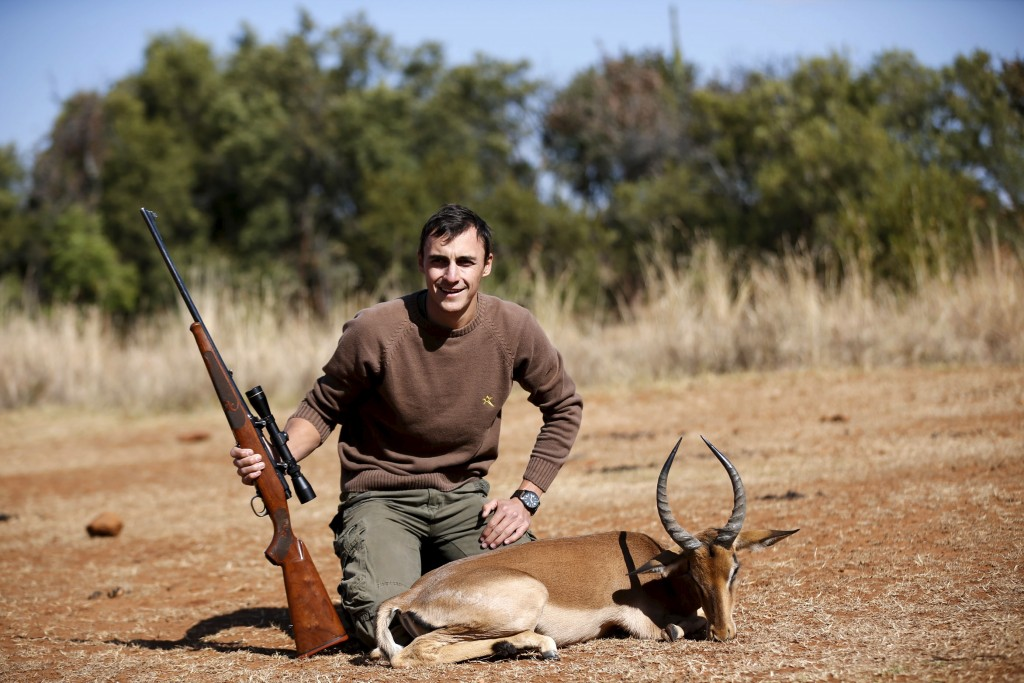 Francois Cloete poses in front of an Impala that he shot at the Iwamanzi Game Reserve in the North West Province, June 6, 2015. Africa's big game hunting industry helps protect endangered species, according to its advocates. Opponents say it threatens wildlife. Now a mooted change in regulations in the United States could affect the number of foreigners who come to Africa to hunt big game, damaging the industry and possibly hurting wildlife. Picture taken June 6, 2015. REUTERS/Siphiwe Sibeko  - RTX1G43K