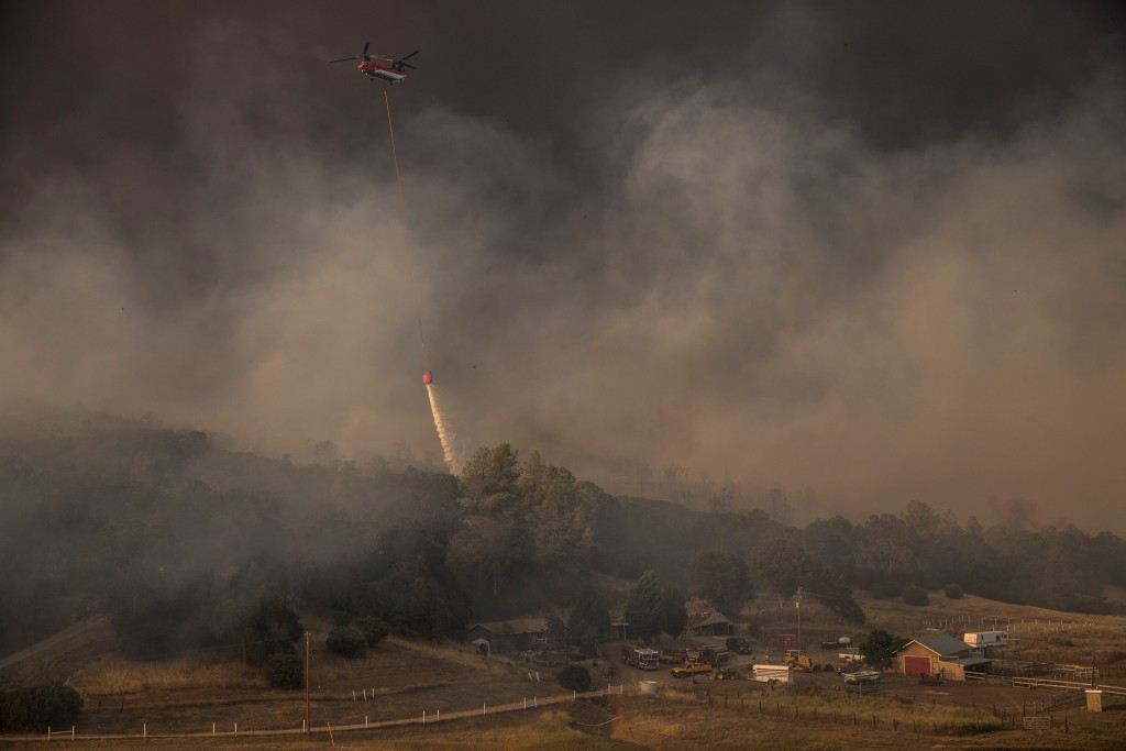 A helicopter drops water to protect a home from the rapidly moving Rocky Fire in Lake County, California July 30, 2015. Photo by Max Whittaker/Reuters